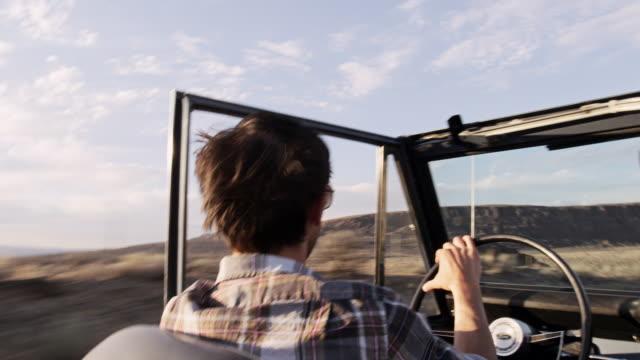 vídeos de stock e filmes b-roll de ms pan man driving convertible off road vehicle on desert road at sunset - convertible