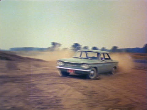 vídeos de stock, filmes e b-roll de 1960 man driving corvair turning corner in dirt + going up hill / industrial - carro esportivo