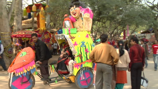 PAN WS Man driving decorated pedicab at Surajkund Fair, Faridabad, Haryana, India