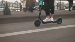Man driving electric push scooter on bridge