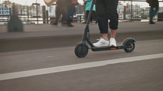 man driving electric push scooter on bridge - motorino video stock e b–roll