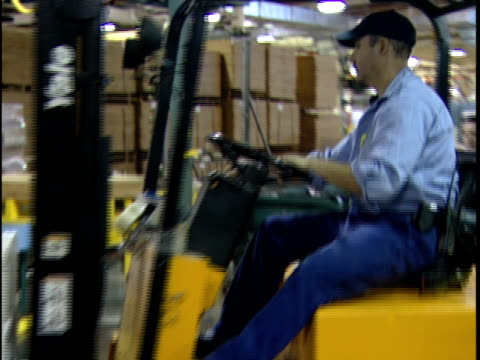 ws zi ms man driving forklift and loading wrapped boxes onto conveyor belt in distribution warehouse / new jersey, usa - forklift truck stock videos and b-roll footage