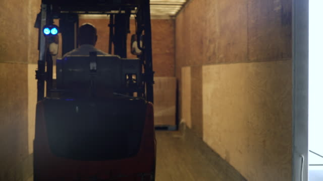 Man driving forklift machinery forward and reversing from warehouse elevator