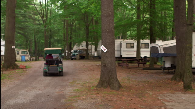 man driving golf cart in trailer park - golf cart stock videos & royalty-free footage