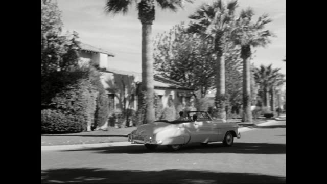ws pan man driving luxury car on street lined with palm trees  / united states - 高級車点の映像素材/bロール