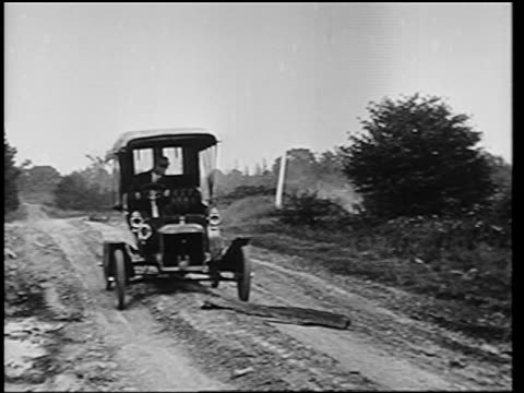 b/w 1905 man driving model n ford on dirt road / he gets out + removes plank / newsreel - ford motor company stock videos and b-roll footage