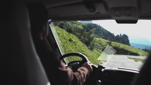vídeos y material grabado en eventos de stock de hombre conduciendo autocaravana en la montaña durante el fin de semana - enfoque diferencial