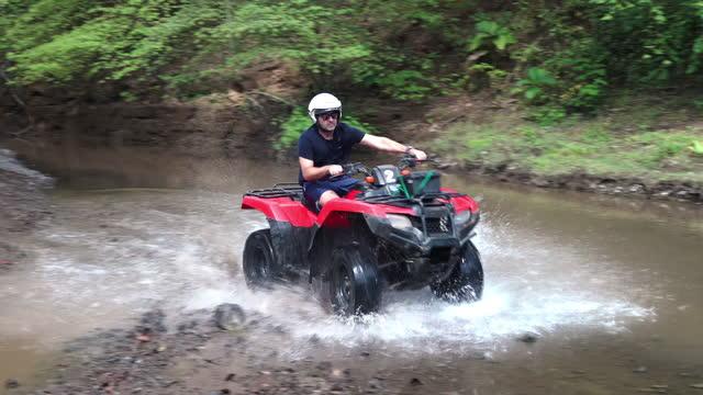 vidéos et rushes de homme conduisant le quad par un petit ruisseau au costa rica - sports utility vehicle