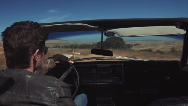 Man driving retro car on dirt road