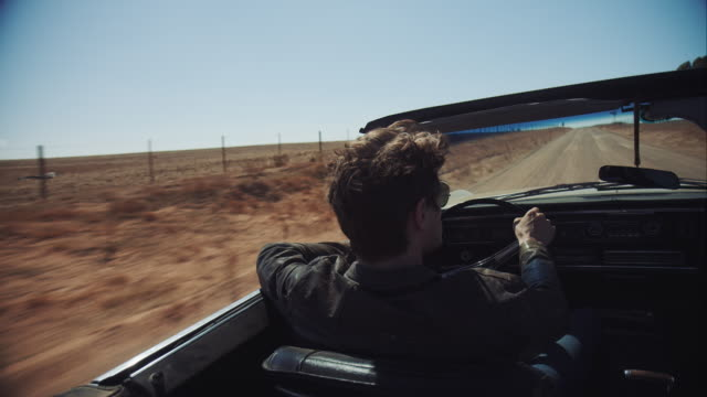 man driving retro car on dirt road - convertible stock videos and b-roll footage
