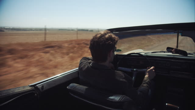 Man driving retro car on dirt road