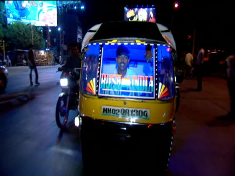 man driving rickshaw with blue light through city traffic at night mumbai - risciò video stock e b–roll