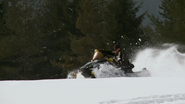 ws pan slo mo man driving snowmobile / pokljuka, triglav national park, slovenia - pokljuka stock videos and b-roll footage