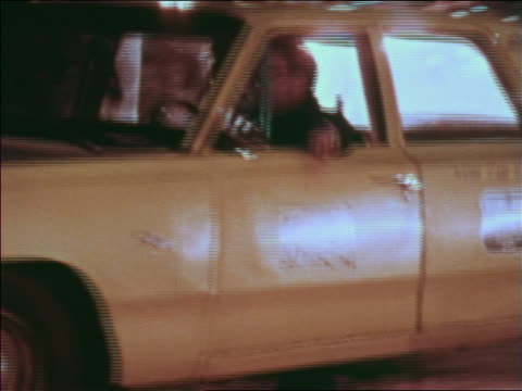 1969 pan man driving taxi past camera on city street at night / greenwich village, nyc - anno 1969 video stock e b–roll
