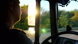 Man driving truck and carefully watching the road. Caucasian guy is riding through countryside with beautiful landscape at background. Profile of lorry driver inside the cab. Slow motion Close up