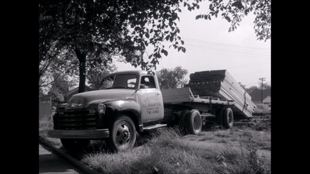 ws man driving truck and unloading timbers on landscape / united states - timber stock videos and b-roll footage