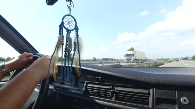 vídeos y material grabado en eventos de stock de hombre conduciendo coches de época en carretera, atrapasueños, colgantes en el espejo retrovisor - estribo de coche