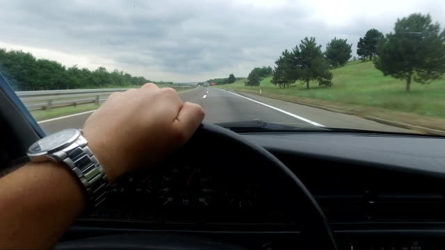 Man driving vintage car on highway, POV