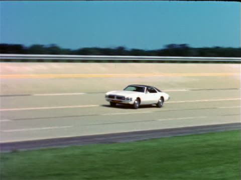 vídeos de stock e filmes b-roll de 1968 pan man driving white oldsmobile toronado on test track / industrial - general motors