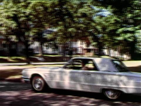 1965 man driving white Thunderbird stopping at stop sign at corner of suburban street / industrial