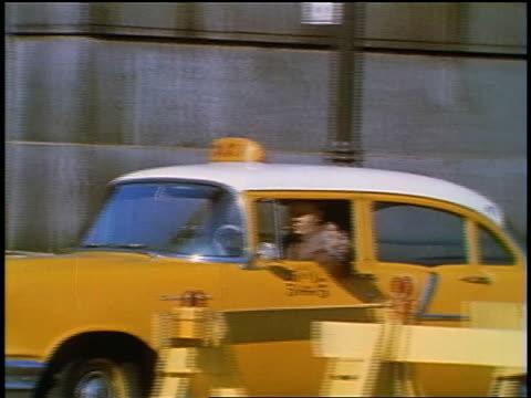 1957 man driving yellow taxi turning towards camera on city street