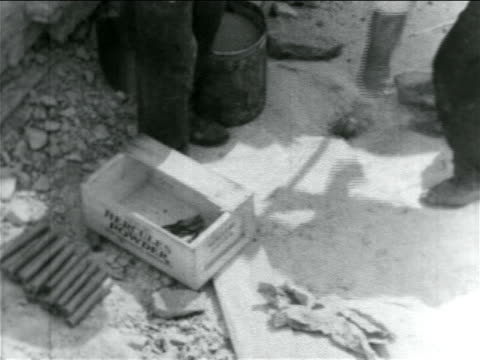 B/W 1934 man dropping dynamite into hole in WPA sewage construction project / documentary