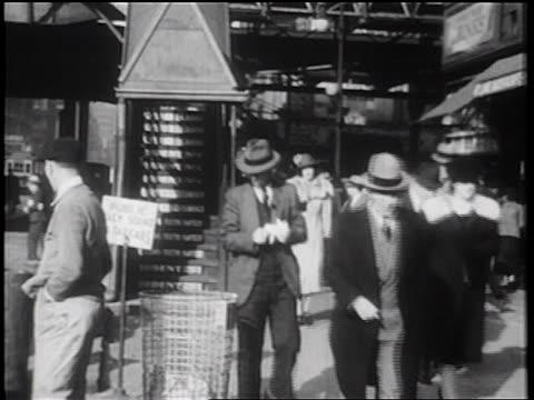 B/W 1939 man dropping newspaper into trash on city sidewalk + man behind picks it up / NYC / doc.