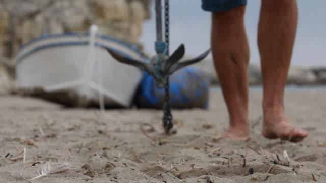 vídeos de stock e filmes b-roll de man drops anchor in sandy beach - ancora