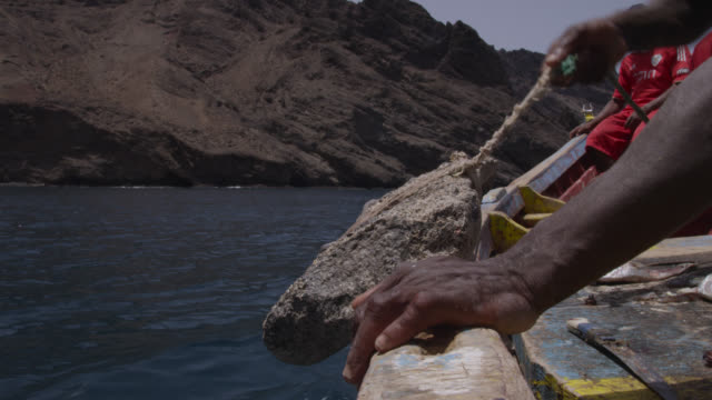 man drops rock anchor from fishing boat, cape verde - adults only videos stock videos & royalty-free footage