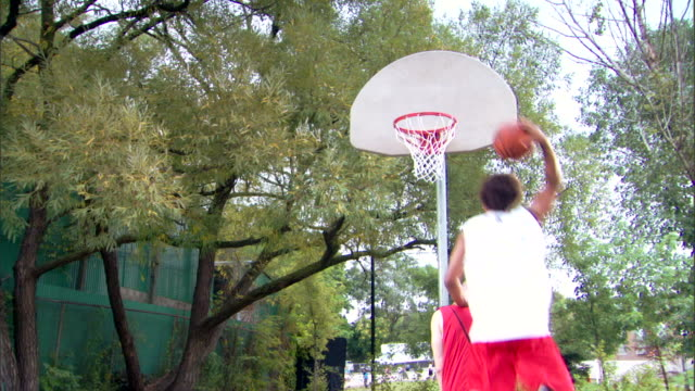 man dunking basketball over other player - see other clips from this shoot 1281 stock videos and b-roll footage