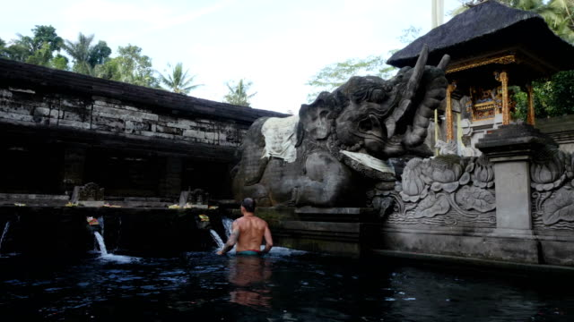 stockvideo's en b-roll-footage met man tijdens ceremonie in tirtha empul tempel (de tempel van de heilige bronwater) in bali - ceremonie