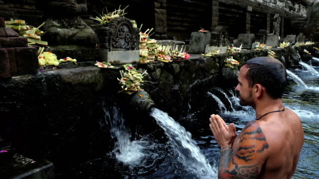 uomo durante la cerimonia nel tempio di tirtha empul (tempio dell'acqua di sorgente santa) a bali - tempio video stock e b–roll