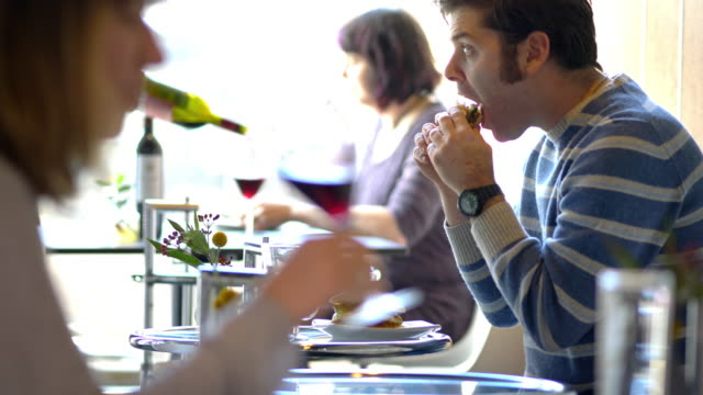 man eagerly eating (biting and chewing) sub sandwich at restaurant - sideburn stock videos & royalty-free footage