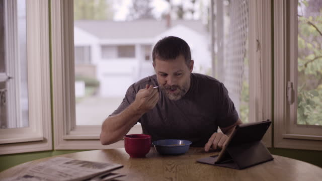 a man east breakfast and reads on his tablet ipad. - t shirt stock videos & royalty-free footage