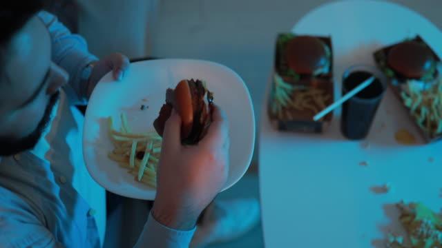 man eating a burger - unhealthy eating stock videos & royalty-free footage