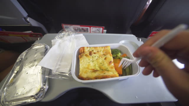 POV man eating airline meal in a flight