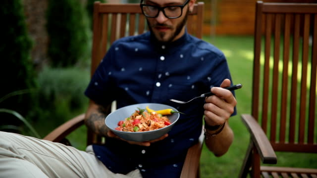 man eating and looking at his laptop in a garden - salad stock videos & royalty-free footage
