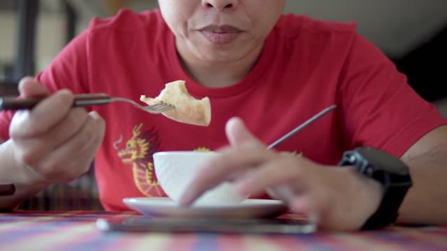 vidéos et rushes de homme mangeant et lisant le message texte sur le smartphone. - bol à soupe