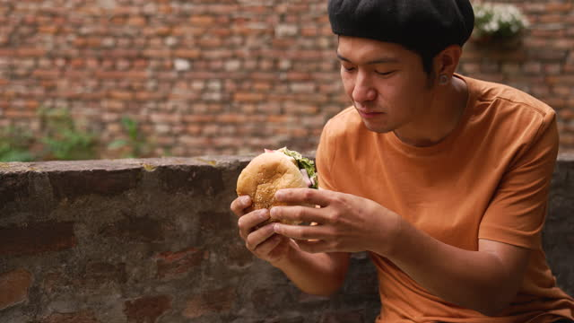 man eating burger outdoors - one mid adult man only stock videos & royalty-free footage