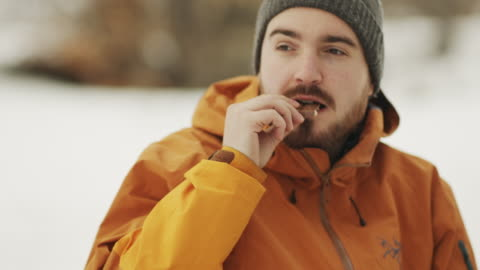 man eating chocolate in the winter forest. stock video - chocolate stock videos & royalty-free footage