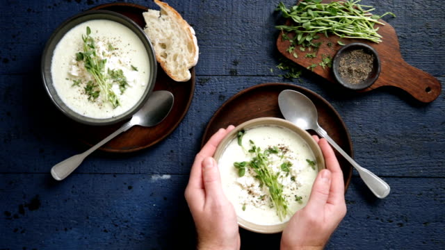 man eating creamy caulflower and broccoli with feta soup - cucina mediterranea video stock e b–roll