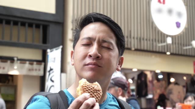 man eating croissant taiyaki (japanese fish-shaped cake). - croissant stock videos & royalty-free footage