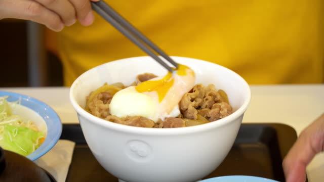男は米と柔らかい bolied 卵でガーリックビーフを食べます。 - fast food点の映像素材/bロール