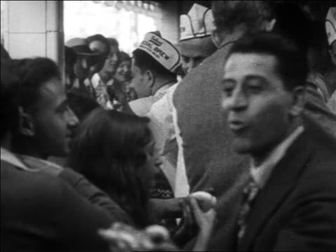 b/w 1930 man eating hot dog near busy hot dog stand / coney island, nyc - coney island brooklyn stock videos & royalty-free footage