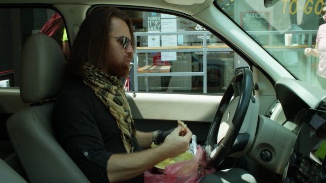 man eating in car during covid-19 lockdown - on the move stock videos & royalty-free footage