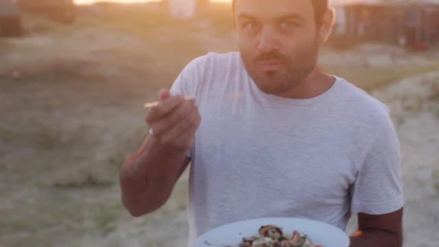 man eating on beach at sunset - endast en man i 30 årsåldern bildbanksvideor och videomaterial från bakom kulisserna