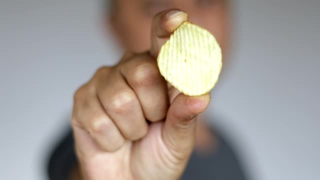 man eating one potato chip - close up - salty snack stock videos & royalty-free footage