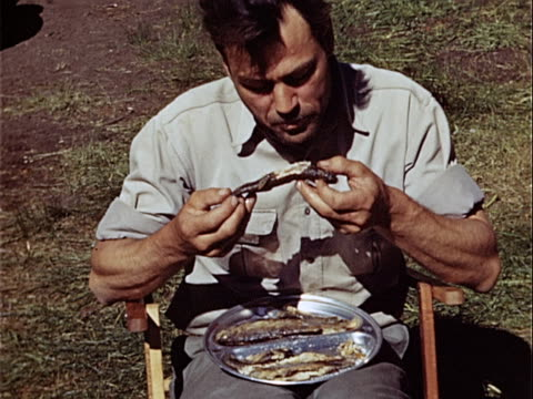 1949 ms man eating plate of fresh caught fish during camping trip / usa  - 1940 1949 video stock e b–roll