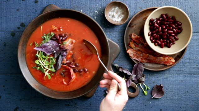 man eating spicy tomato, bean, herb and fried bacon soup - salsa di pomodoro video stock e b–roll