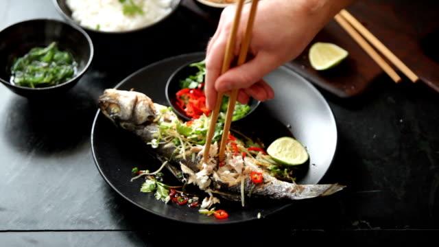 Mann isst gedämpften Seebass